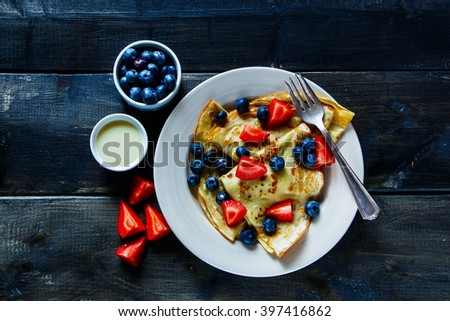 Freshly made thin pancakes or crepes with fresh berries and cream on plate over rustic wooden background, top view.  - stock photo