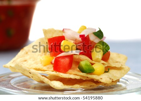 Freshly made tortilla chips with a corn and tomato salsa - stock photo
