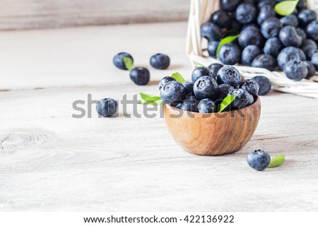 Freshly picked blueberries in wooden bowl.fresh blueberries with  leaves on a white rustic table. selective focus. - stock photo