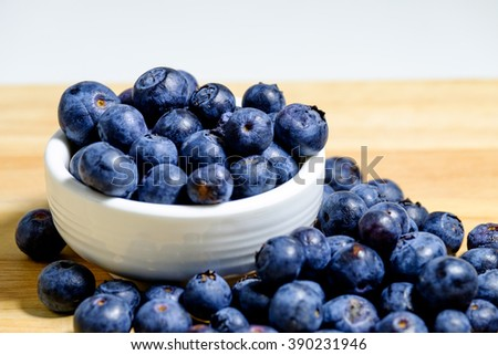 Freshly picked blueberries in wooden bowl. Juicy and fresh blueberries on wooden Background Selective Focus