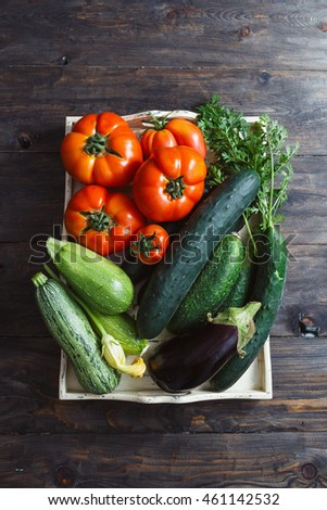 Freshly picked organic homegrown vegetables in box on wooden table