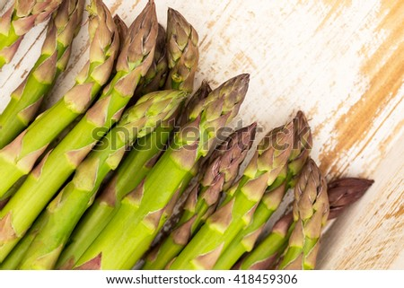 Freshly picked raw asparagus on white  wooden background, close up, Flat Lay - stock photo
