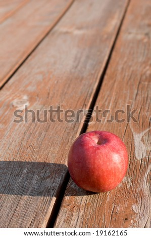 Freshly picked red apple on weathered picnic table - stock photo