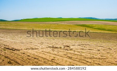 Freshly plowed summer topsoil dirt on production field - stock photo