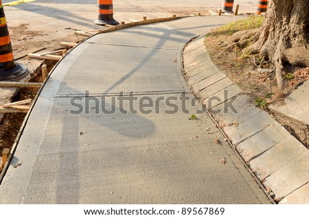 Freshly poured cement on sidewalk upgrade - stock photo