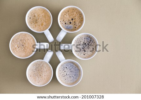 Freshly poured coffee topped with frothy bubbles arranged in a circular radiating design with converging handles on a beige background with copyspace, overhead view