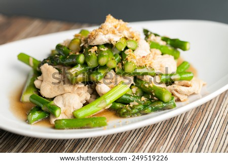 Freshly prepared Asian style chicken and asparagus stir fry with garlic - stock photo