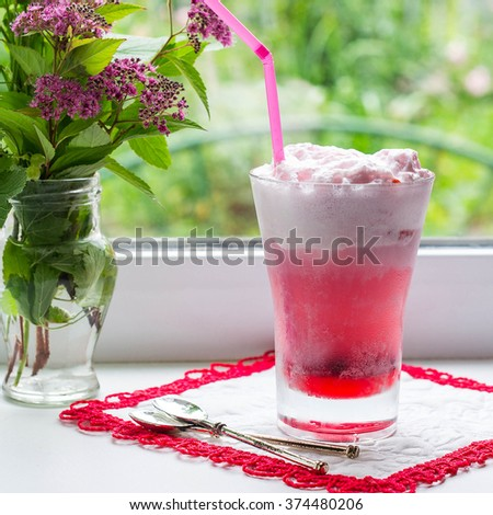 Freshly prepared fruit cocktail with ice cream and bouquet of flowers in the pot at the window. Selective focus, square image  - stock photo