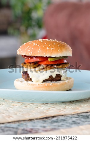 Freshly prepared home made beef cheeseburger with fresh onions, mushrooms, tomatoes and pickles. No lettuce. - stock photo