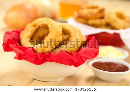 Freshly prepared homemade beer-battered onion rings in a bowl with napkin with dips on the side (Selective Focus, Focus on the front of the onion ring on the right) - stock photo