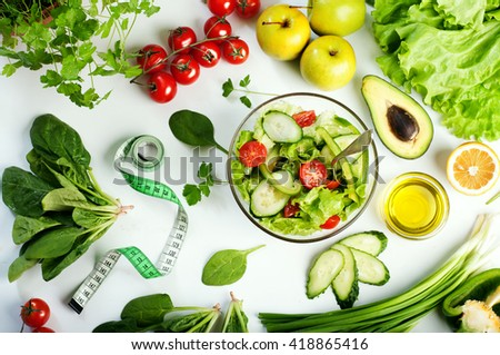 Freshly prepared salad vegetables. Concept diet food. White background. The variety of vegetables and herbs next to the plate with a salad. - stock photo