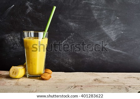 Freshly prepared tall glass filled with banana almond smoothie and green straw next to nuts and banana over wood table with copy space on wall - stock photo