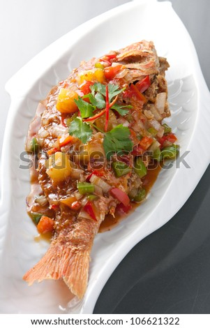 Freshly prepared Thai style whole fish red snapper dinner with tamarind sauce. - stock photo
