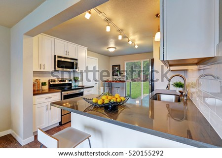 Freshly remodeled kitchen room with white cabinetry and gray counter tops. Northwest, USA