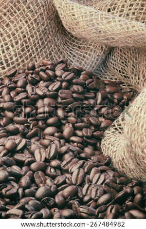 Freshly roasted coffee beans with a burlap background. Image has been filteres to reduce contrast and saturation slightly. - stock photo