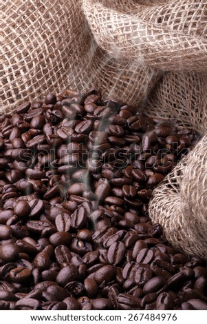 Freshly roasted coffee with a burlap background - stock photo