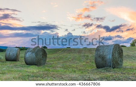 Freshly rolled bales of hay are seen on a rolling hill during a storming sunset - stock photo