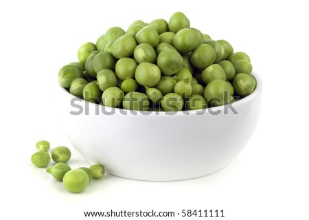 Freshly shelled green peas, in a small white bowl.