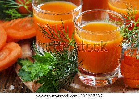 Freshly squeezed carrot juice in glasses, selective focus - stock photo