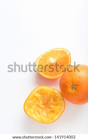 Freshly squeezed orange half with whole and segments on white background - stock photo