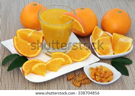 Freshly squeezed orange juice and vitamin c tablets with oranges over bamboo background. - stock photo