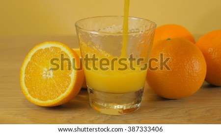 Freshly squeezed orange juice close-up, pouring into glass on wooden background. - stock photo