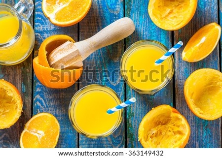 freshly squeezed orange juice in a glass with straws with slice of fruits - stock photo