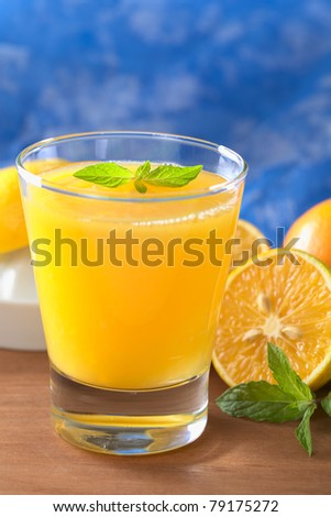 Freshly squeezed orange juice with orange slice and mint leaf on top of the juice with a blue background (Selective Focus, Focus on the mint leaf on top of the juice) - stock photo