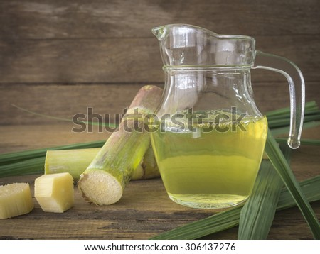 Freshly squeezed sugar cane juice in jug with cut pieces cane on a wooden table. - stock photo