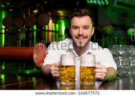 Freshly tapped beer. Handsome smiley bartender stretching out beer mugs and smiling - stock photo