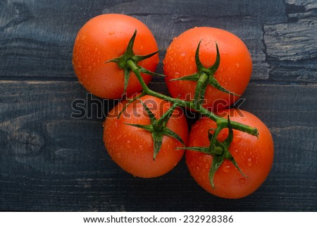Freshly washed ripe juicy tomatoes on rustic board - stock photo