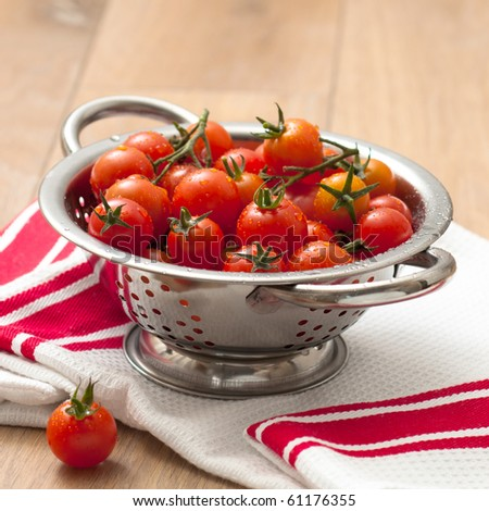 Freshly washed ripe tomatoes in colander on kitchen table - stock photo