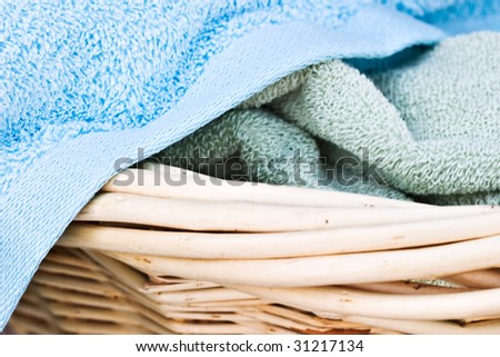 Freshly washed towels in a laundry basket - stock photo