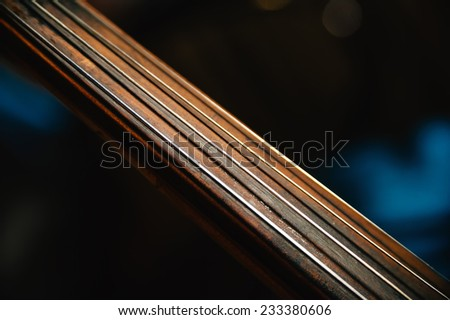 fretboard of old shabby cello on a black backgrounds. Selective soft focus on string