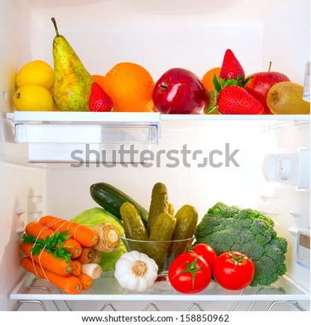 Fridge full of healthy fruits and vegetables - stock photo