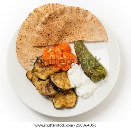 Fried aubergine (or eggplant) and fried mild green peppers served with garlic infused tomato and yogurt sauces. This is a traditional Turkish summer dish, served cold. - stock photo