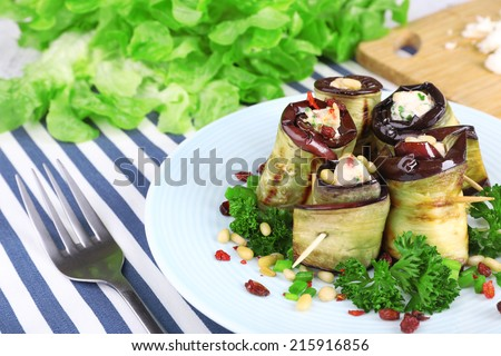 Fried aubergine with cottage cheese and parsley on a napkin on wooden background