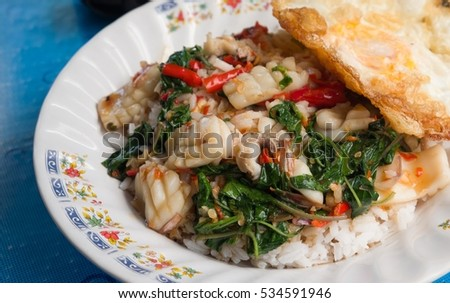 Fried basil leave with squid and fried egg on steamed rice.