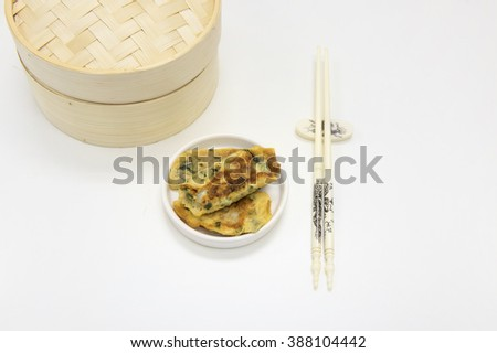 Fried beat egg and garlic chives mixture to thin sheet and wrap over fish paste.  Serve in eating Chinese dim sum setting with bamboo  basket and a pair of chopsticks.  White background. - stock photo