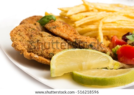 Fried beef cutlets with potato chips and salad