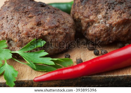 Fried beef cutlets with spices, rustic dark wooden background