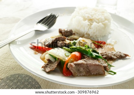 fried beef with oyster sauce,white dish spoon and fork, on table background photo - stock photo
