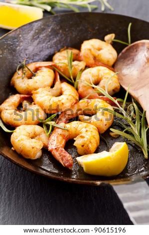fried black tiger prawns with fresh rosmarin and lemon - stock photo
