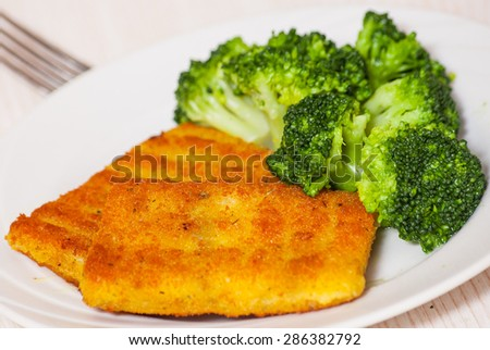 fried breaded fish fillets with broccoli - stock photo