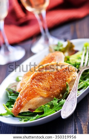 fried chicken breast with salad leaves on the plate - stock photo