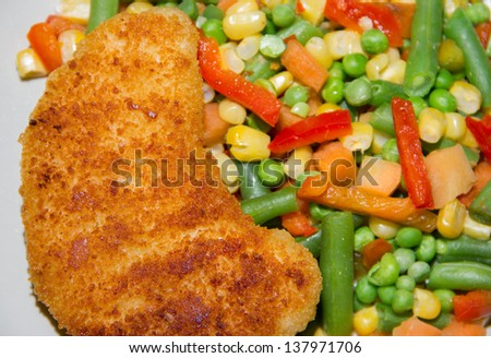 Fried chicken breast with vegetables close up. - stock photo
