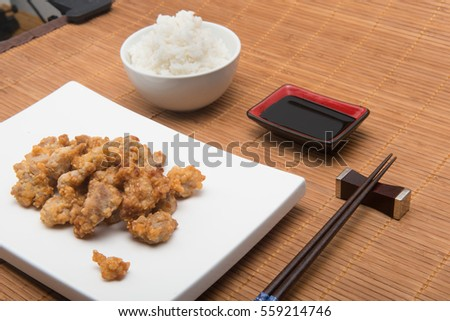 fried chicken chinese stile with rice and chopsticks