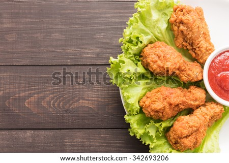 Fried chicken drumstick and ketchup on wooden background. - stock photo