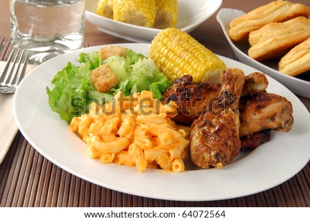 Fried chicken drumsticks with salad and macaroni and cheddar cheese - stock photo