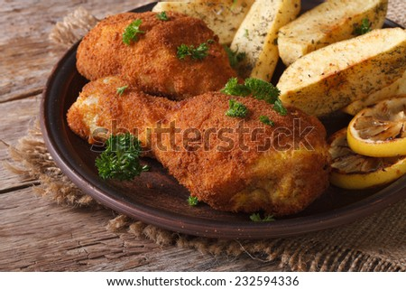 fried chicken legs dipped in batter, with a garnish on a plate close up on an old table horizontal  - stock photo
